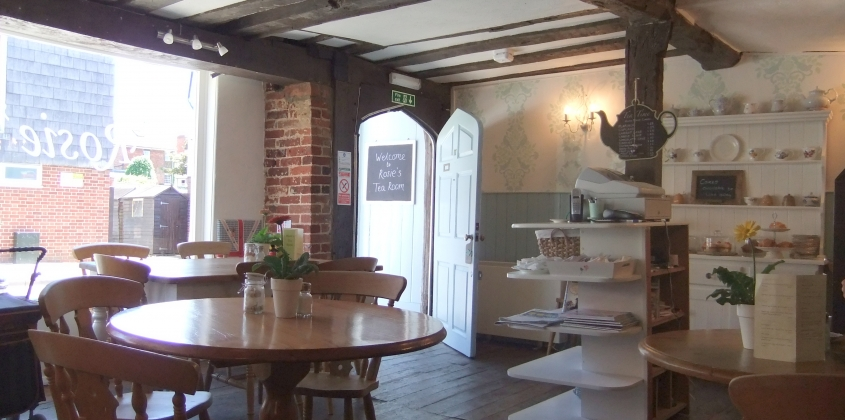 Inside a traditional tea room with farmhouse tables and a dresser full of pretty china
