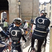 Cyclists in very professional looking gear massing ready to set out on a ride