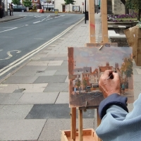 looking over an artists shoulder as he completes an oil painting on Bridge Street