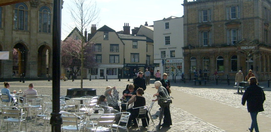 looking across the Market Place towards the High Street, cafe tables and people walking across the space