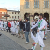 Morris dancers showing visiting students how to dance whilst a dog looks on