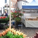 Colourful market stalls, with vegetables, bread and flowers