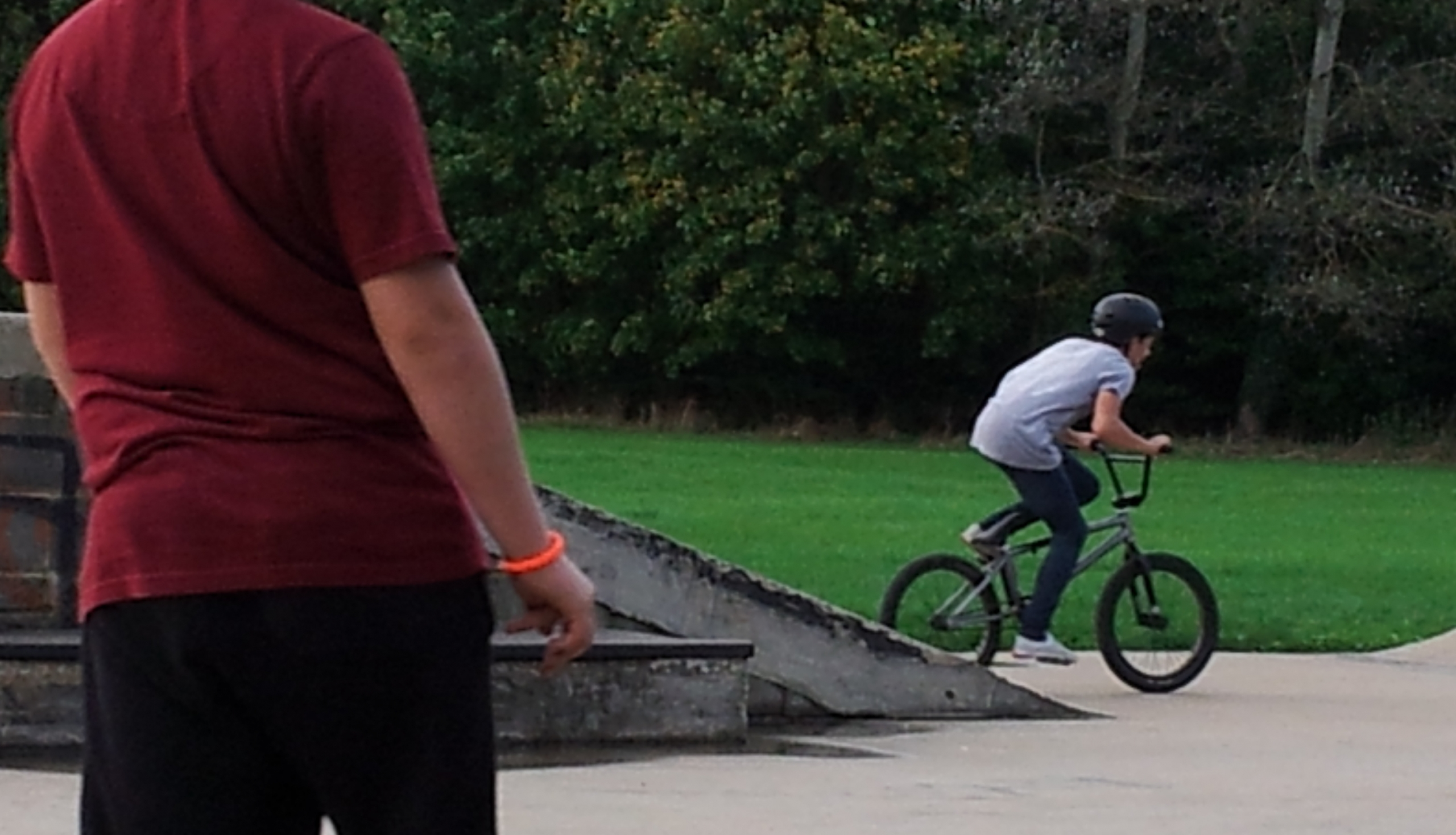 Skateboarder stops to watch BMXer go for a trick