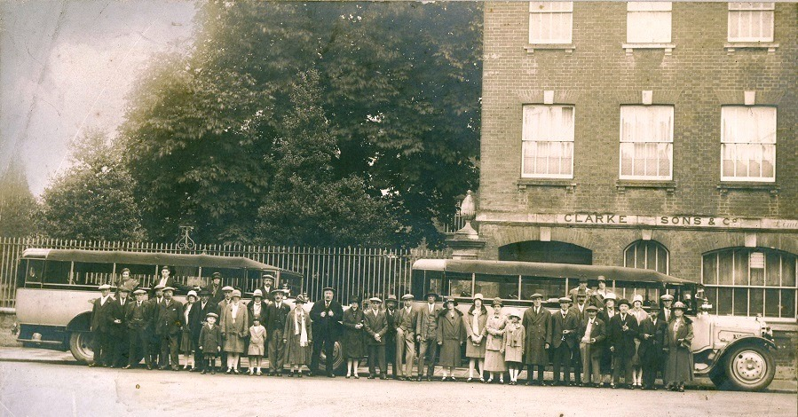 Outside the clothing factory in the 1920s with workers ready to leave on a factory outing.